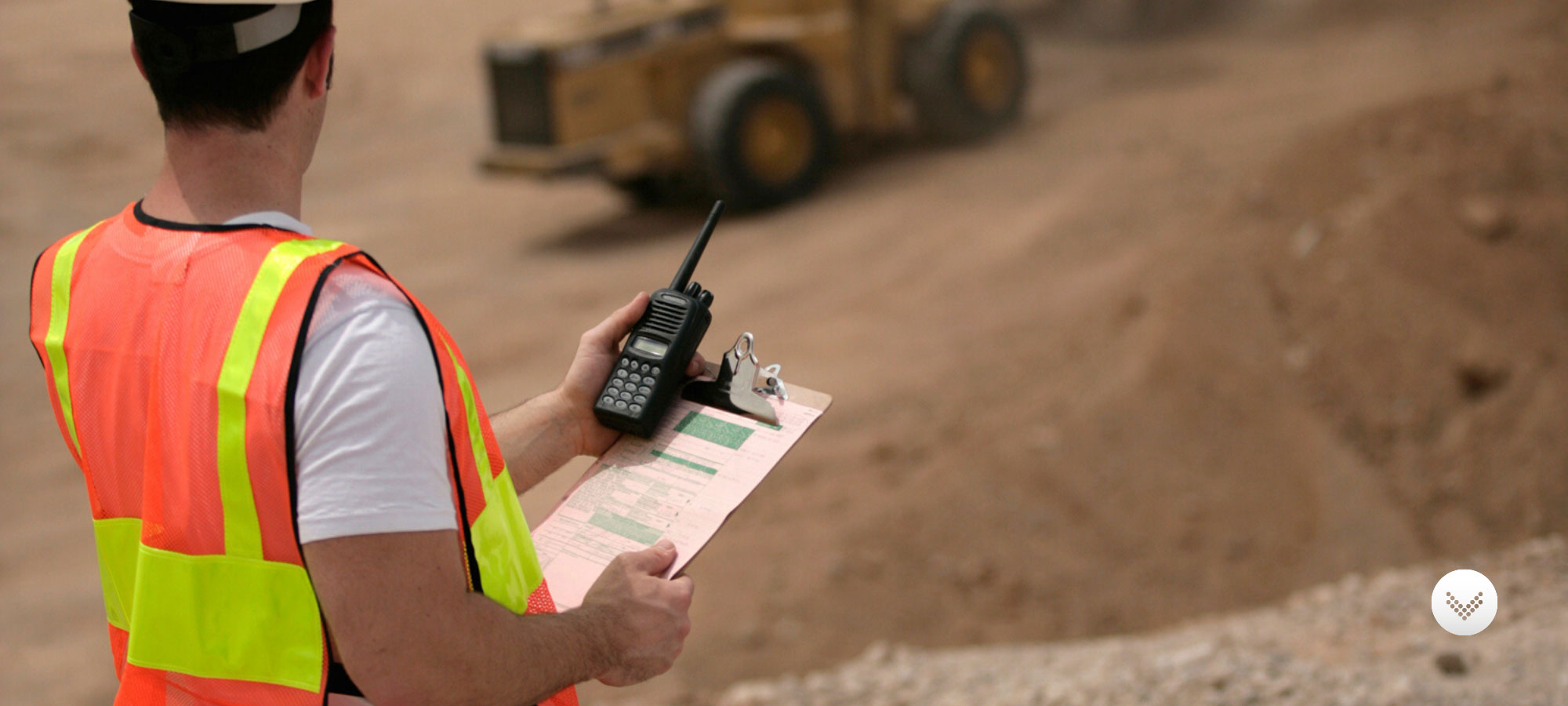 Construction worker holding clipboard and Kenwood two-way radio on dirt construction site with equipment in the background.