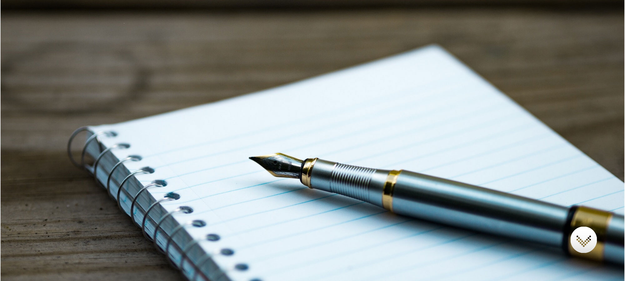 Fancy pen and note pad of paper situated on a wooden desk.