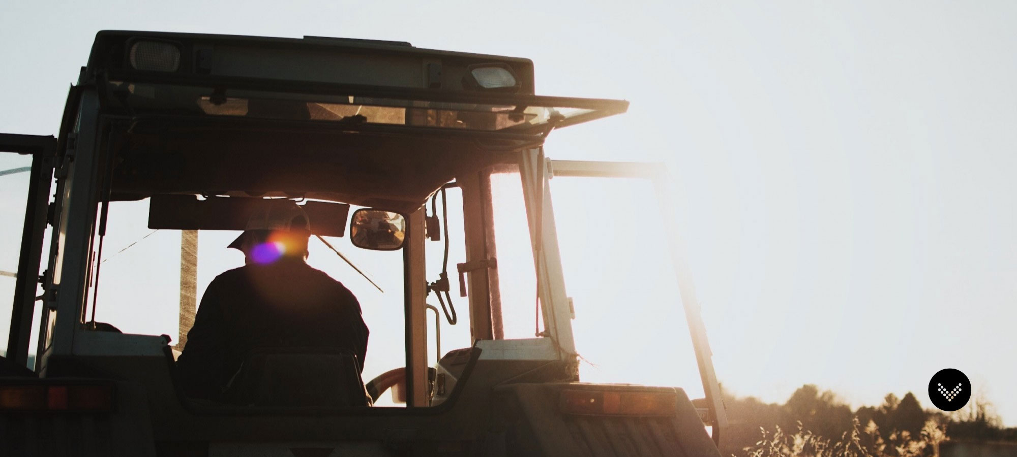 Sun shinning down on a farmer driving a tractor through the field