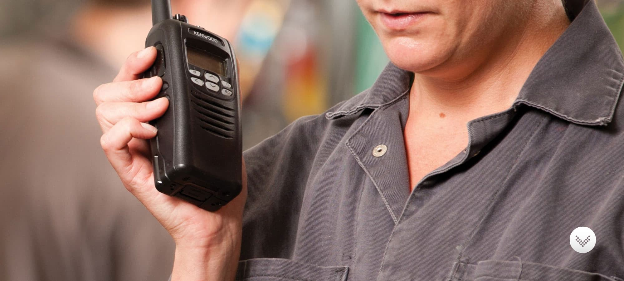 Female factory worker using a kenwood two way radio on the factory floor.