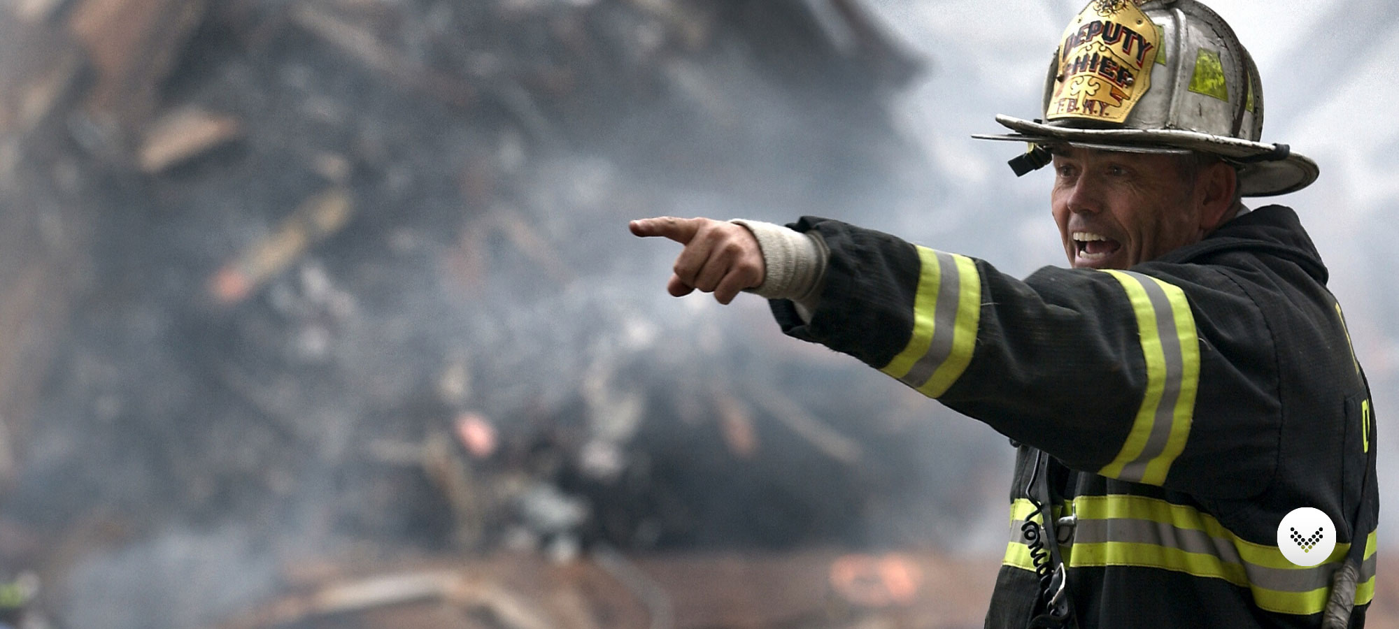 Fire fighter pointing at something and yelling commands on the scene of a disaster.