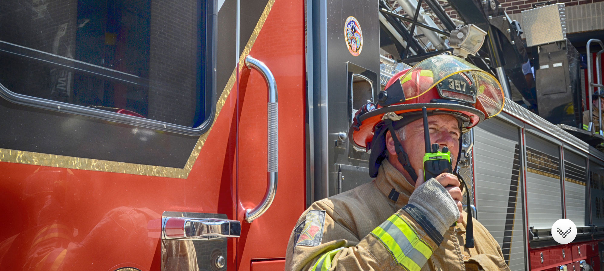 Fire fighter using a high visibility Kenwood two way radio while standing in front of a fire truck.