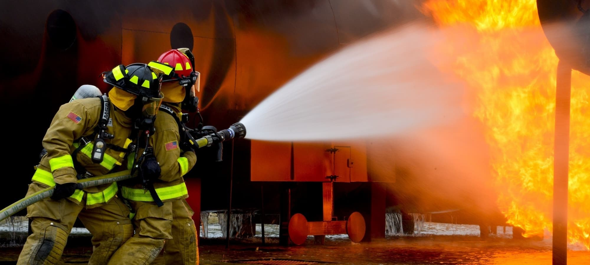 Two firefighters using a fire hose to put our a large fire.