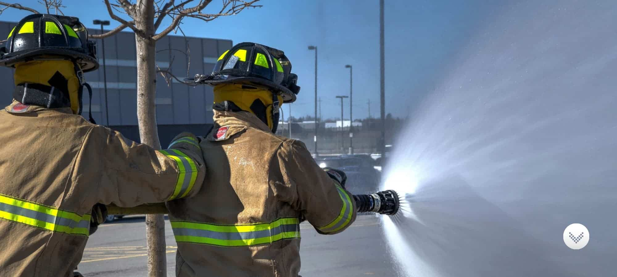 Two fire fighters dispensing water from a fire hose.