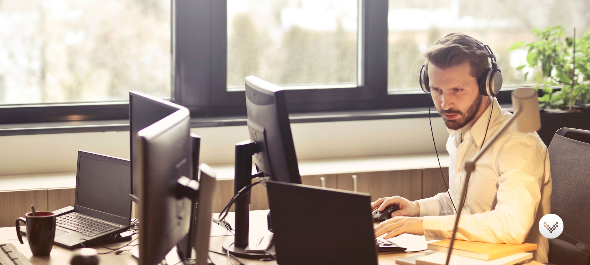 Male sitting at desk monitoring a computer screen while wearing wired headphones.